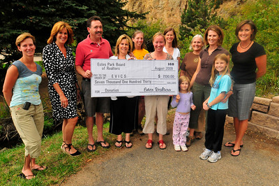 Photo by Walt Hester EVICS board receives a check from the Estes Park Board of Realtors on Thursday. The Board of Realtors gave $7,130 to the EVICS.