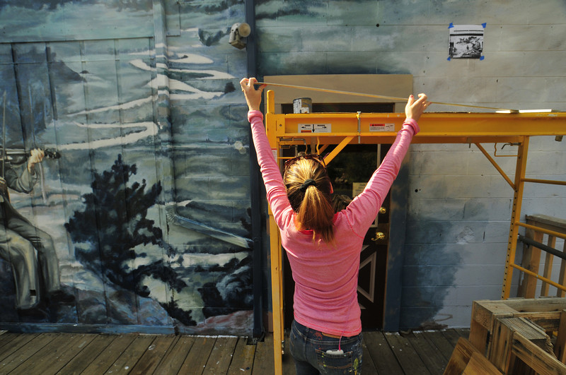 Photo by Walt Hester<br /> Artist Ella Yates prepares to paint behind the Cultural Arts Council and Local Roots Co-op on Wednesday. Yates hopes to finish her mural by October.