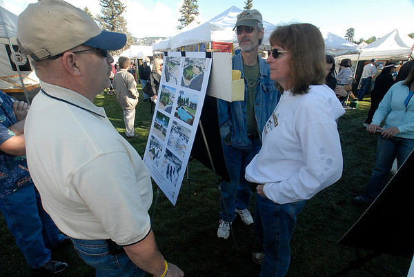 Photo by Walt Hester<br /> Mayor pro-tem Chuck Levine shows visitors plans for the redevelopment of Bond Park during the arts and crafts show in the park on Saturday. Visitors were encouraged to vote on their favorite design for the park.