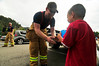 "Photo by Walt Hester<br /> Estes Park fire fighter Luke Smith gives a balloon to Gage Jacobson, 4, of Loveland in front of Bond Park on Elkhorn Avenue Sunday. The Estes Park Volunteer Fire Department again participated in the Labor Day ""Fill the Boot"" to raise money for the Muscular Dystrophy Foundation."