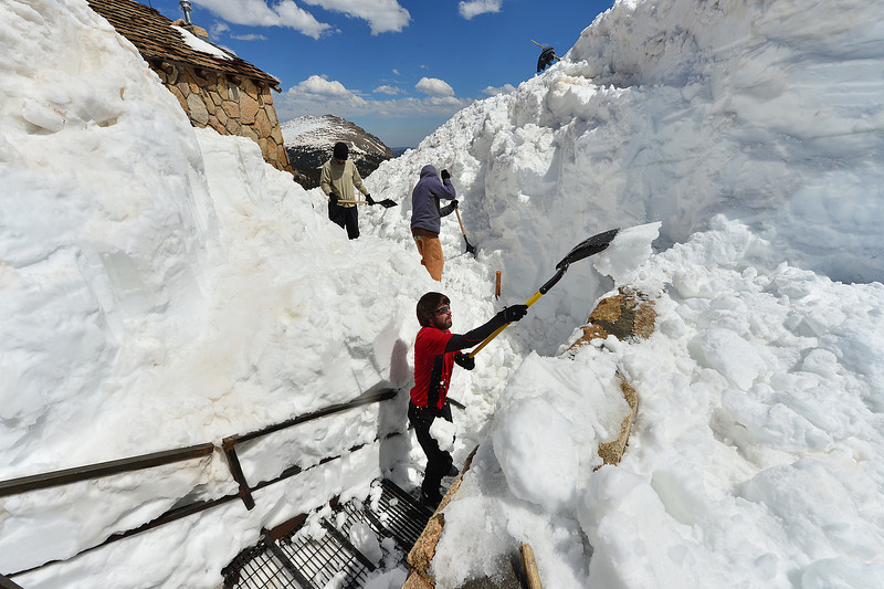 Workers dig out a stairway aroung the Trail Ridge Store in Rocky Mountain National Park on Friday. The national park opened the nation's highest continuous highway over the Continental Divide on Friday.