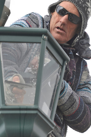 Walt Hester | Trail-Gazette<br /> Donny Yager cleans a lamp along Moraine Avenue on Wednesday. The painter was picking up extra work during colder days.