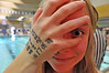 Walt Hester | Trail-Gazette<br /> Freshman swimmer Maddy Paul clowns at the photographer's request to show the numbers on her hand. At big meets, swimmers often keep track of their events by writing on themselves.