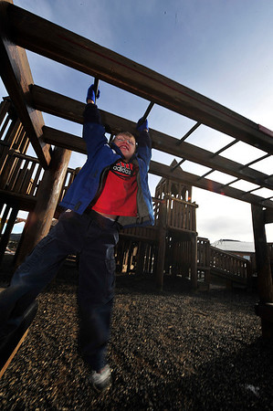 Walt Hester | Trail Gazette<br /> Estes Park first-grader Blake Honeycutt enjoys the unusually warm January morning on the monkey bars on Wednesday. While snow is possible on Friday, temperatures will tease the 40s this weekend.