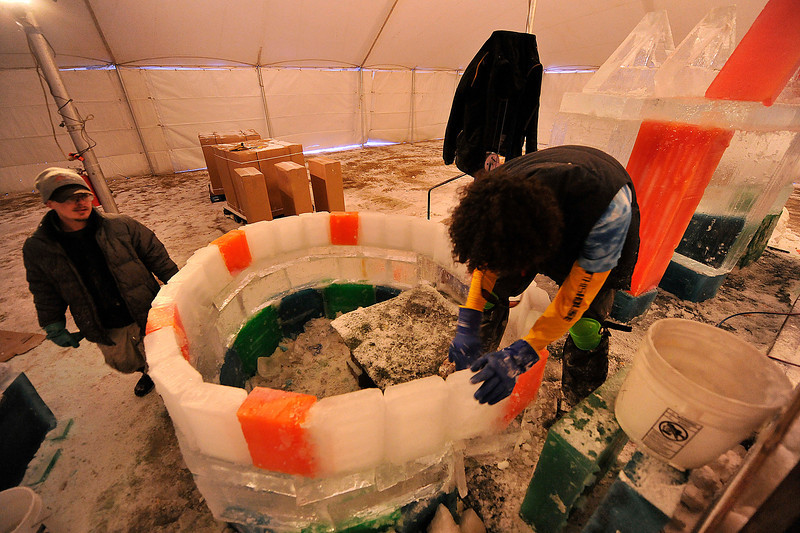 Walt Hester | Trail Gazette<br /> Joel Ward watches Joaquin Botello apply slush to the gaps between ice bricks at the Stanley Fairgrounds on Wednesday. Cool Hand Ice Carving is creating a candyland-style ice castle for this weekend's Estes Park Winter Festival.