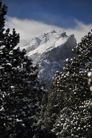 Walt Hester | Trail Gazette<br /> Hallett Peak looms over Bear Lake Road. Snow and clouds finished the scene over the Continental Divide.
