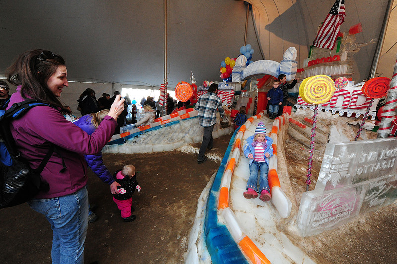 Walt Hester | Trail Gazette<br /> Jennifer Bertino of Arvada photographs her daughter, Alicia, on the slide of the Candy Land ice sculpture at the Estes Park Winter Festival on Saturday. The sculpture was protected from the weekend sun by a tent, which kept visitors slipping and sliding all weekend long.