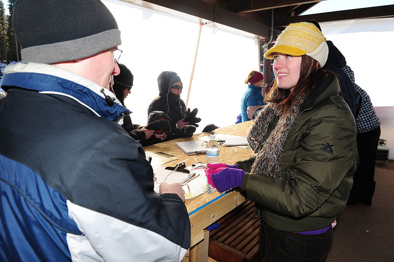 Walt Hester   Trail Gazette<br /> Nicole Arnold signs up and orients visitors to the annual Winter Trails Day on Saturday. The booth at the Bear Lake Park and Ride was the first thing visitors encounter when they visited.