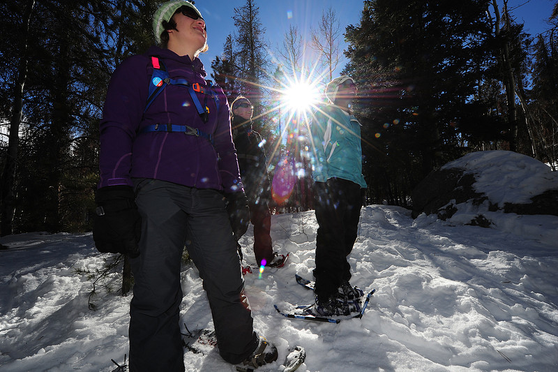 Walt Hester | Trail Gazette<br /> Tracy Louk, Catherine Wilkinson and Rabekah Bodden, all from Denver, watch friends pound down and adjacent hillside during the Winter Trails Day. Consumers were able to take snowshoes out on trails close to the Bear Lake Park and Ride to test them out.