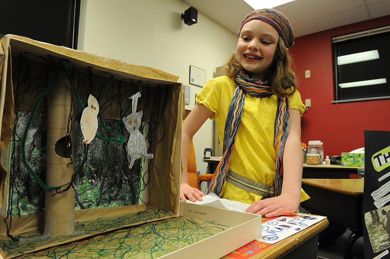 Walt Hester | Trail Gazette<br /> Maddie Moellers, 8, shows her pride in her bush babie display at the elementary school's Africa Night. The school's third-graders study Africa, then show off what they have learned about clothing, wildlife and culture during their annual program.