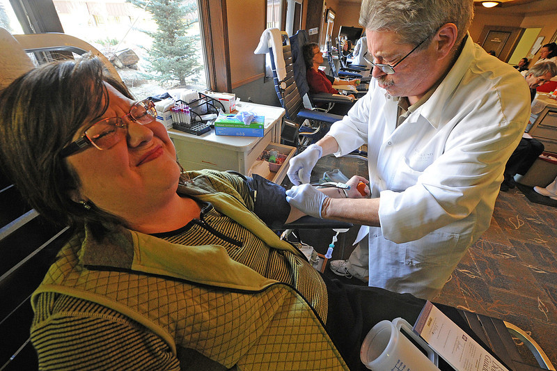 Walt Hester | Trail Gazette<br /> PJ O'Connor of Estes Park grimaces as Dan Bolden sticks her with a needle at the Red Cross Blood Drive on Monday. Organizers reported 118 donors for the drive.
