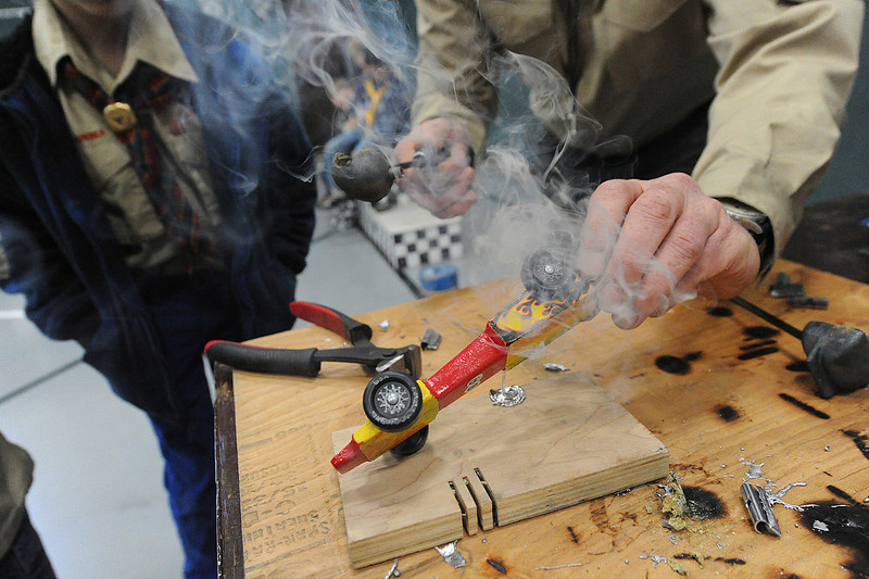 Walt Hester | Trail Gazette<br /> Daniel Gosnell pours melted metal into the bottom of a pinewood derby car at the race on Saturday. The derby brings out many tools to help the cars move as fast as possible.