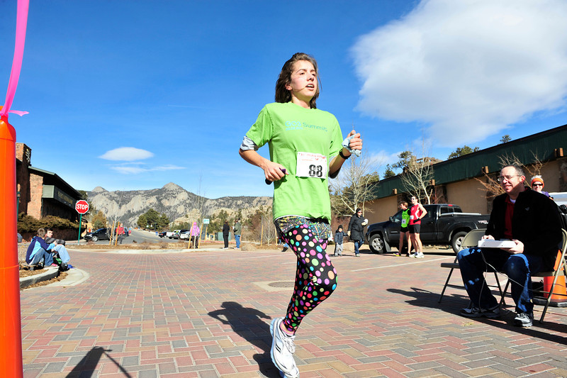 Walt Hester | Trail Gazette<br /> Estes Park teen-ager Kelsi Lasota crosses the finish line of the 5k race on Sunday. Lasote placed third among women in the shorter race.