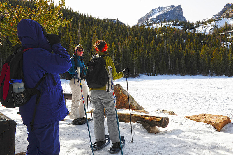 Walt Hester | Trail Gazette<br /> From left, Donna Coggins of Greeley, Lindsay MacDonald and Aya Webster, both of Denver, admire Bear Lake and Hallett Peak on Wednesday. The outing was the Denver residents' first on snowshoes.