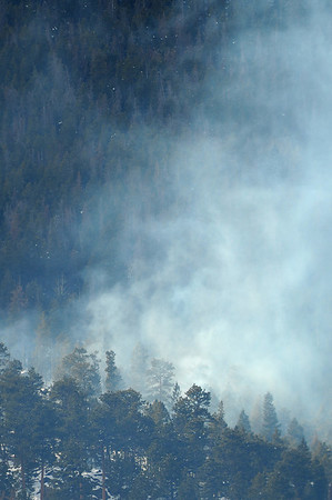 Walt Hester | Trail Gazette<br /> Smoke rises from slash pile burning on the east side of Deer Mountain on Wednesday. With chilly temperatures, new snow and little wind, the national park has moved ahead on controled burns.
