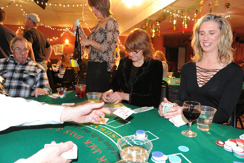 Walt Hester | Trail Gazette<br /> Heidi Riedesel, far right, takes a card during a game of blackjack at the Sunrise Rotary Club's annual Casino Night at the Village Playhouse on Saturday. The event raises money for the club's scholarships.