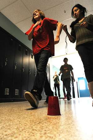 Walt Hester   Trail Gazette<br /> Martha Sologuren,13, right, times classmate Marcus Kingston, 14, over a marked, 100 meter stretch of hallway at the Estes Park Middle School on Wednesday. The students are studying physics and using the exercise to graph motion.