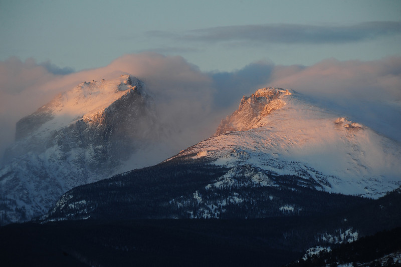 Walt Hester | Trail Gazette<br /> Wednesday's first light paints the tops of Hallett Peak and the Dragons Tail area of Flattop as they emerge from morning clouds. Snow is not expected to return to the area until Monday.