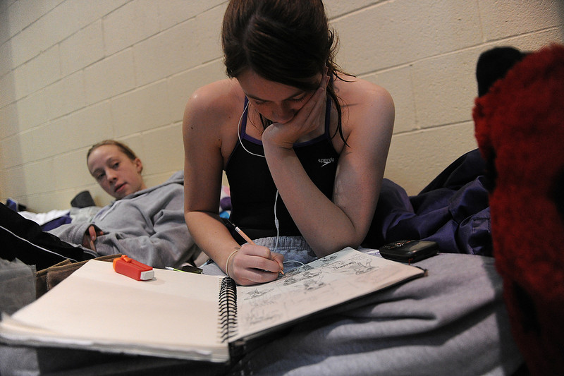 Walt Hester | Trail Gazette<br /> Freshman Holli Holmes lounges as senior Kassie Fisher draws during Saturday's session at the 4A swim finals. Each swimmer has a different strategy for relaxing.