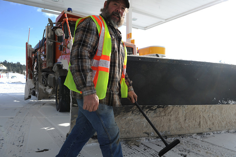 Walt Hester | Trail Gazette<br /> Colorado Department of Transportation plow driver Mike McCleary cleans the mirrors of his plow after a morning of work along HWY 7 on Saturday. McCleary started plowing around midnight.
