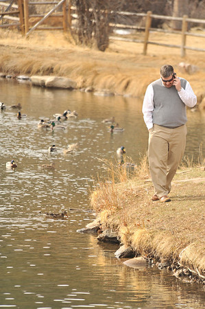 Walt Hester | Trail Gazette<br /> A man enjoys a phone conversation by a pond along Moraine Avenue on Wednesday. Friday and Saturday should see sunshine and warm temperatures before the possibility of snow returns on Sunday.