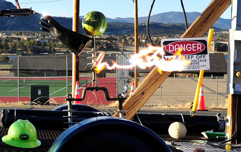 Walt Hester | Trail Gazette<br /> Estes Park's Light and Power demonstrate the hazards of live wires on a metal and melon mannequin in the High School parking lot on Wednesday. The town workers took the opportunity of the middle school's science fair for their demonstration.