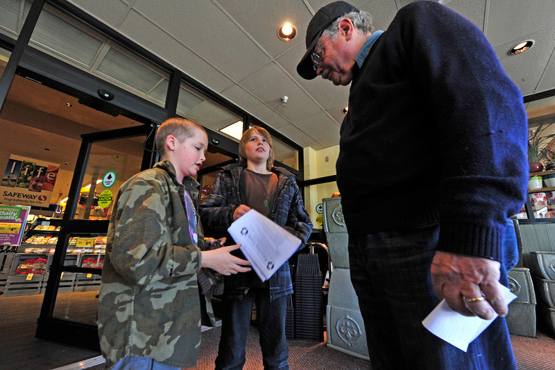 Walt Hester | Trail Gazette<br /> Max Walter, left, and Cole Watts, both 12, talk to Peter Plaut at Safeway about recycling on Friday. The middle school's Shuttle Bugs and the League of Women Voters gave away 50 grocery gabs, provided by Safeway, to promote recycling.