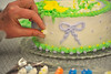 Walt Hester | Trail Gazette<br /> Dena Bohn places one more flower on her cake on Tuesday. Cake decorating was one of many district-outreach classes offered this spring.