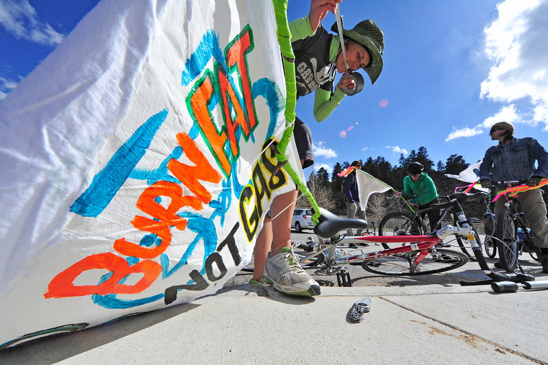 Walt Hester | Trail Gazette<br /> Alex Wieser of Estes Park attaches a banner to the back of her bike before the Progressive Estes Critical Mass ride on Friday. The small group of cyclists celebrated people-powered locomotion as well as Earth Day.