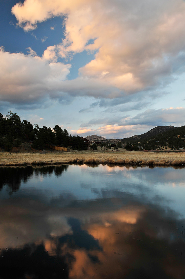 Walt Hester | Trail Gazette<br /> Clouds break up and float off in the sky and in its reflection on a pond in Carriage Hills on Wednesday. Warm weather and clear skys are expected for Duck Race weekend in Estes Park.