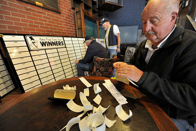 Walt Hester | Trail Gazette Ed Acela peels stickers at the Wheel Bar on Monday identifying Duck Race prizes so they can be adheared to a board for all to see. The boards will be ondisplay for the annual Estes Park Duck Race on Saturday.