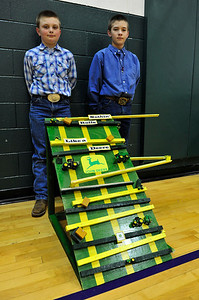 Walt Hester | Trail Gazette Heath Rasmussen, 10, and Hunter Kitchens, 11, show off their John Deere-themed marble run on  Thursday. The elementary school's annual marble run competition challenges students to create a run in which a marble will keep moving, but will take the longest time to get rom the start to the finish.
