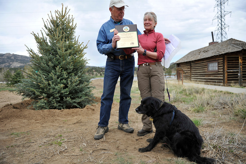 "Walt Hester | Trail Gazette<br /> Janise Reichstadt accepts the Estes Valley Environmental Stewardship Award on Monday from Estes Park mayor Bill Pinkham in honor of her late husband, Howard Burkhart. The posthumous award recognized Burkhart's ""Outstanding contributions to the natural environment, especially in the area of successful forestry and tree management."