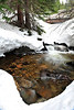 Walt Hester | Trail Gazette<br /> Melting snow exposes a small stretch of Glacier Creek on Tuesday.