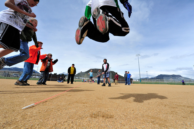 "Walt Hester | Trail Gazette<br /> Elementary schoolboys leap in an effort to avoid a pole during a game of ""Helicopter"" on Wednesday at the Stanley Ball Fields. The game was one of many played during the Estes Park Elementary School's annual field day."