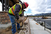 Walt Hester | Trail Gazette<br /> Moses Ramos of Coulson Excavating lays a block on top of a retaining wall at the Stanley Park Transit Hub on Wednesday. The hub should be complete by mid-June.