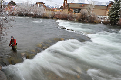 Walt Hester | Trail Gazette A fly fisherman casts for a bite in the Blue River as it courses through the Outlet Mall of Silverthorn on Friday. Fly fishing is extremely popular throughout Colorado, no matter what the background.