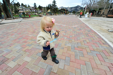 Walt Hester | Trail Gazette Lucy Krank, 2, of Bouder enjoys ice cream while strolling across the new bricks of MacGregor Avenue on Wednesday. Officials expect the Bond Park project to be completed for the Memorial Day weekend.