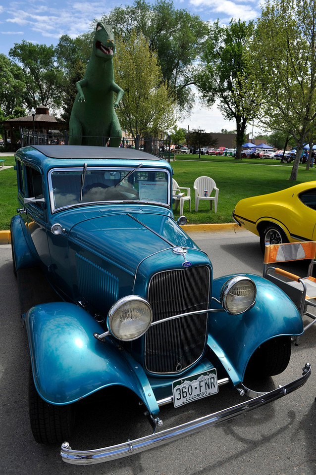 Walt Hester | Trail Gazette<br /> Fruita's famous t-rex stands over a classic Ford sedan on Saturday. Fruita, known for the Colorado National Monument, mountain biking and dinosaurs also celebrates Mike the Headless Chiken Days in late May, with music, a petting zoo, a running race and a classic car show.