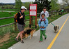 "Walt Hester | Trail Gazette<br /> Lisa Campbell and dog, Henry, of Nywott, Macy Ryan, 10, of Boulder and Beth Rauh with her dog, Kasey, turn on the Lake Estes Trail after encountering the ""No Dogs"" sign on Wednesday. Elk are calving along the trail and can be aggressive toward people and dogs."