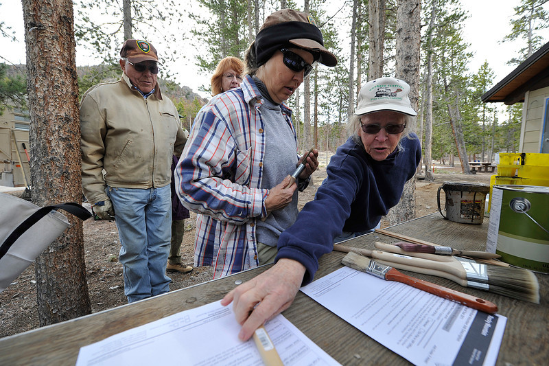 Walt Hester | Trail Gazette<br /> Kay Franklin of Estes Park reaches in front of Paula Malleck of Longmont as volunteers get started at the Glacier Basin Campground on Thursday. The volunteers were painting a restroom at the campground.