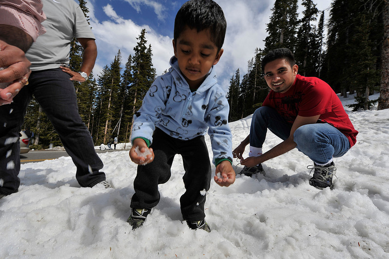 Walt Hester | Trail Gazette<br /> Rithvic Deepak, 2, and Mandeep Randhawa, both of Westminster, play in the snow above Trail Ridge Road on Sunday. Impressive drifts hem in the road well below Rainbow Curve where the road is still closed.