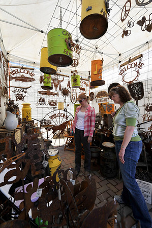 Walt Hester | Trail Gazette<br /> Visitors admire unique metal art by Bartlett Art Works at the Estes Park Art and Craft Market in Bond Park on Sunday. The market was the first major event of the summer traval season.