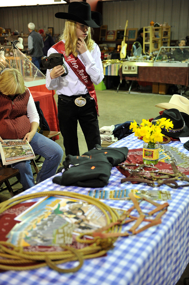 Walt Hester | Trail Gazette<br /> Rooftop Rodeo princess Lexi Life looks to tag items at the rodeo's table at the annual Estes Park Antique Show on Saturday. Pie safes, snowshoes brands and more could be found at the show.