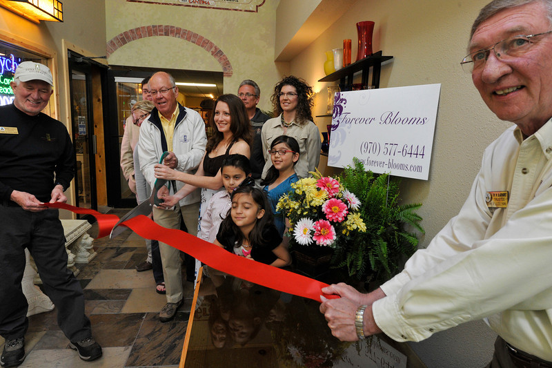 Walt Hester | Trail Gazette<br /> Town officials help cut the ribbon on a new Estes Park business, Forever Blooms, on Tuesday. From left, trustee Mark Elrod, Mayor Bill Pinkham, business owner Jennifer Collins, Lowell Richardson, Elizabeth Fogarty, twins Johnathan and Jennifer Mark, 6, Melina Mark, 8, trustee Eric Blackhurst. Obscured by Mayor; Dawn Shields and Adam Mark.