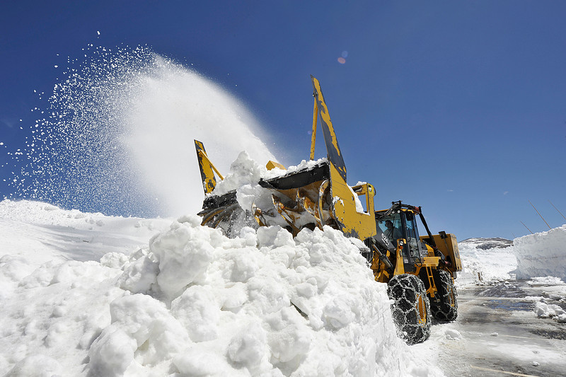 Walt Hester | Trail Gazette<br /> A large rotary plow clears record snow off the lot at the Alpine Visitors Center on Friday. Some drifts at the Fall River Pass were estimated between 25 and 30 feet high.