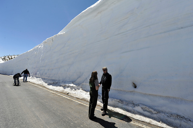 Walt Hester | Trail Gazette<br /> Park Public Information Officer Kyle Patterson speaks to Nick Mole of Estes Park about the snow, forming a wall 16-20 feet tall behind them near Ute Trail on Friday. The Colorado snowpack is reported at about 240 percent of the 30-year average.