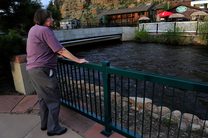 Walt Hester | Trail Gazette<br /> Elizabeth Rogers of Estes Park watches the rising Big Thompson River near the Post Office parking lot on Friday. Estes Park residents are watching and preparing as area rivers rise as a result of record snow pack in the national park.