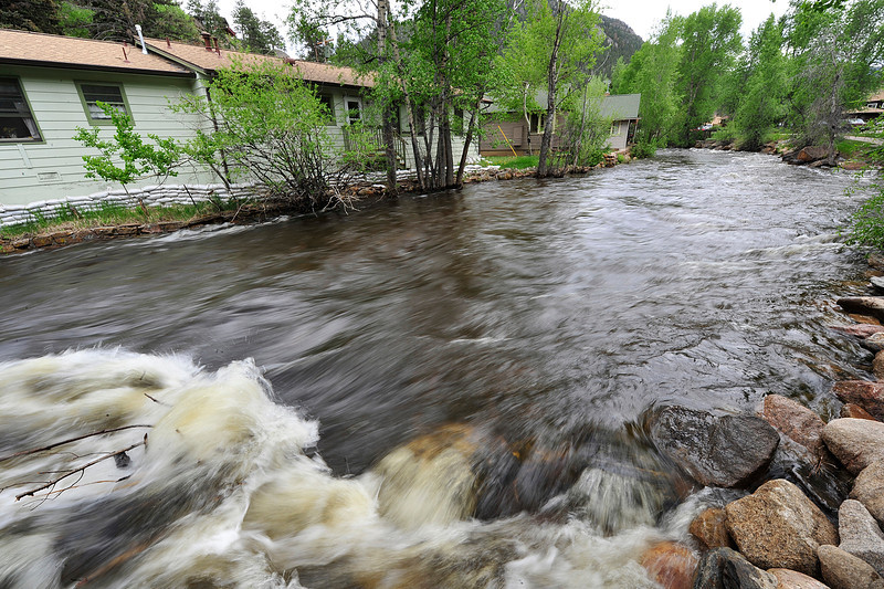 Walt Hester | Trail Gazette<br /> The Big Thompson River rushes past a sand-bagged home on Wednesday. WHile an overnight storm brought river levels up, the rivers are still within their banks around Estes Park.