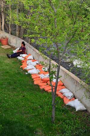 Walt Hester | Trail Gazette<br /> Kaaki Tamushyo of Estes Park sits on sandbags along the Big Thompson River behind her family's restaurant on Friday. While record snow hampers the opening of Trail Ridge Road, the snow's runoff could cause flooding in Estes Park as early as Sunday into early Monday.